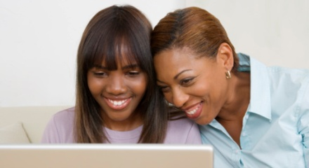 Teen and mother looking at laptop